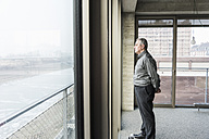 Senior businessman looking out of window - UUF09995