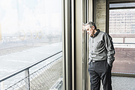 Exhausted senior businessman leaning against window - UUF09998