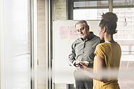 Woman talking to businessman in office - UUF10007