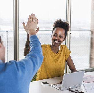 Happy young woman high fiving with colleague in office - UUF10010
