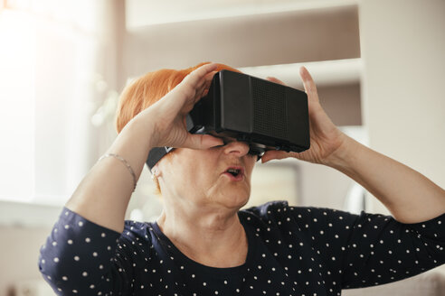 Senior woman at home wearing VR glasses - ZEDF00531