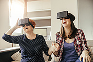 Excited adult daughter with mother at home wearing VR glasses - ZEDF00534