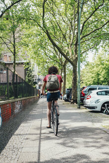 Young man riding bicycle on pavement - RTBF00713