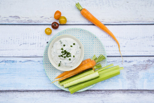 Bowl of herb yoghurt dip and vegetable sticks on plate - LVF05921
