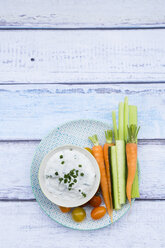 Bowl of herb yoghurt dip, cherry tomatoes and vegetable sticks on plate - LVF05924