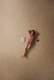 Woman lying on carpet wearing headphones, top view - JOSF00632