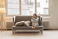 Woman sitting on couch looking sideways - JOSF00635