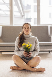 Woman with closed eyes sitting on floor holding flower - JOSF00644