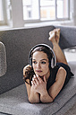Woman lying on couch wearing headphones - JOSF00647