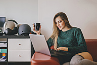 Young woman relaxing on the couch with cup of coffee using laptop - LCUF00109