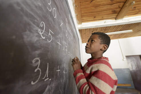 Madagaskar, Boy in Fianarantsoa elementary school calculatiing at blackboard - FLKF00758