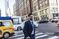 Businessman in the streets of Manhattan with yellow cab in background - GIOF02071