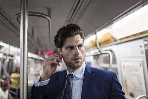 Businessman in metro using smart phone - GIOF02074