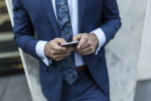 Businessman leaning on a wall in the city, using smart phone - GIOF02092