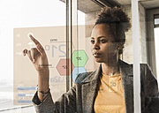 Young woman touching glass wall with data in office - UUF10060