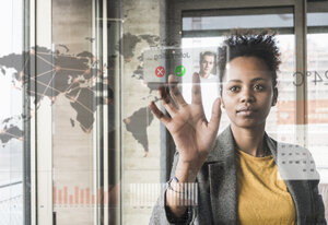 Young woman receiving a call on glass wall with world map in office - UUF10072
