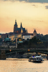 Czechia, Prague, view to castle and Charles Bridge with Vltava in the foreground at sunset - CSTF01311