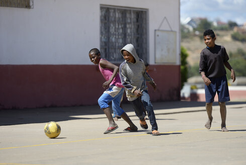 Madagascar, Fianarantsoa, Boy playing soccer in school yard - FLKF00775