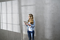 Blond woman with tablet in front of grey wall looking at distance - FMKF03562