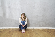 Smiling blond woman sitting on the floor in front of grey wall - FMKF03565