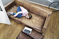 Woman relaxing on leather couch at home - FMKF03568