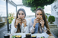 Portrait of two women holding hamburgers in a street restaurant - KIJF01301