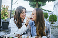 Young woman feeding her friend in a street restaurant - KIJF01304