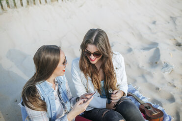Two young women sitting on the beach looking using cell phone - KIJF01310