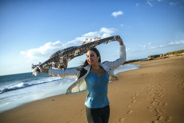 Young woman with blanket in the wind on the beach - KIJF01313