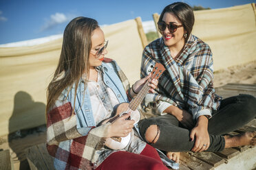 Woman playing ukulele on the beach while her friend watching her - KIJF01316