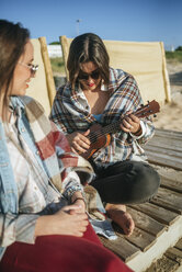 Woman playing ukulele on the beach while her friend watching her - KIJF01319