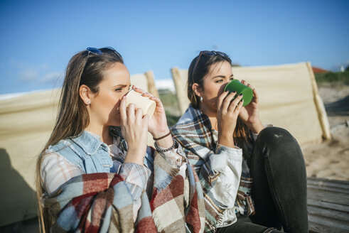 Two young women drinking coffee on the beach - KIJF01322