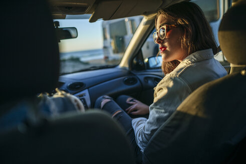 Young woman with sunglasses in car at evening twilight - KIJF01328