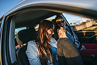 Two young women traveling in a car - KIJF01334