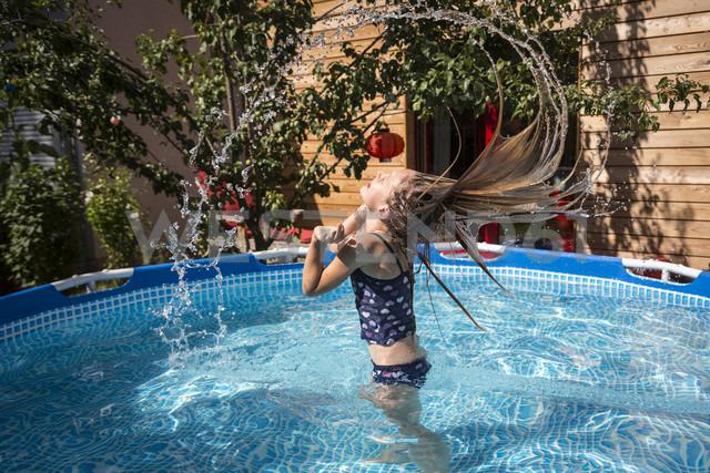 Girl in the garden pool splashing with water - SARF03219