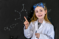 Portrait of girl wearing work coat and safety glasses in front of blackboard with chemical formulas - SARF03220
