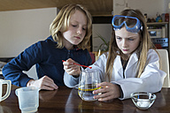 Two children using chemistry set at home - SARF03223