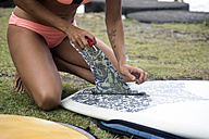 Woman preparing surfboard on meadow - KNTF00648