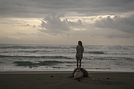 Indonesia, Java, back view of woman standing on the beach at evening twilight - KNTF00652