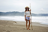 Indonesia, Java, portrait of woman standing on the beach - KNTF00658