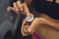 Indonesia, Java, tanned woman taking suncream out of tiny pot, close-up - KNTF00661