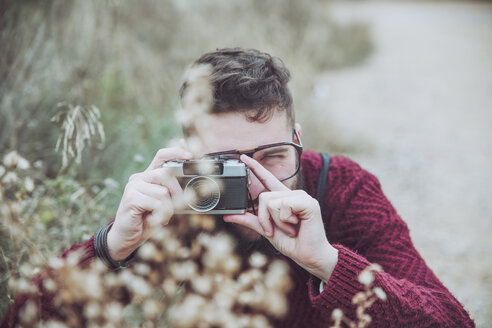 Bearded man taking photo of flowers with vintage camera - RTBF00721