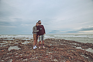 Young gay couple standing hand in hand on the beach - RTBF00724