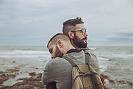 Young gay couple hugging on the beach - RTBF00727