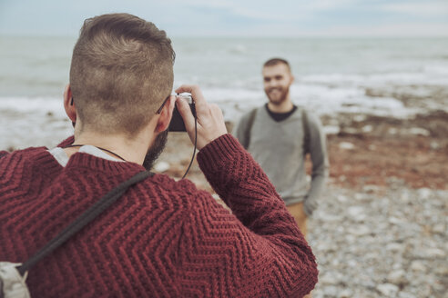 Man taking photos of his boyfriend in front of the sea - RTBF00733