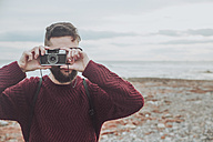 Bearded man taking photo on the beach with vintage camera - RTBF00736