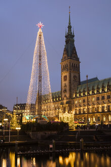 Germany, Hamburg, steel Christmas tree at market in front of illuminated town hall - WIF03401