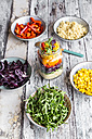 Glass of rainbow salad with bulgur, rocket and different vegetables and bowls with ingredients - SARF03242