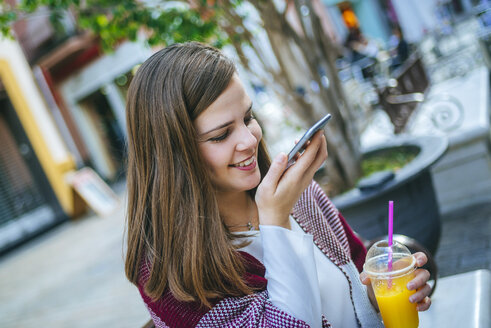 Young woman in Sevilla drinking fruit juice and sing smart phone - KIJF01338