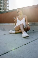 Relaxed woman sitting in armchair on rooftop in Brooklyn - GIOF02099